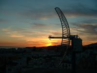 Parabolic antena with the Andalusian sunset in the background pointing at Tangiers